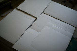 Chipboard box tops, die cut, ready to pop out, fold, glue, and label.